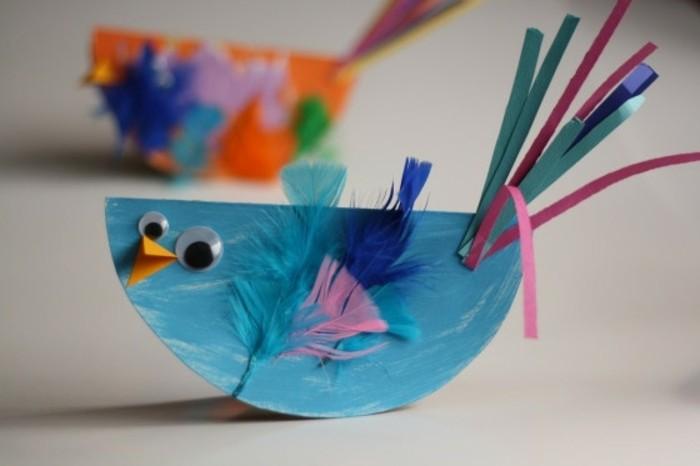 un poussin couleur bleu avec des plumes, des yeux mobiles, bec en papier et queue en bandes de papier, activité manuelle maternelle