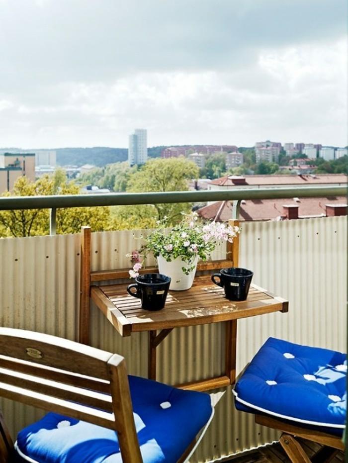 decoration balcon, tasses de café noires, pot à fleurs blanc, housses de coussin bleues