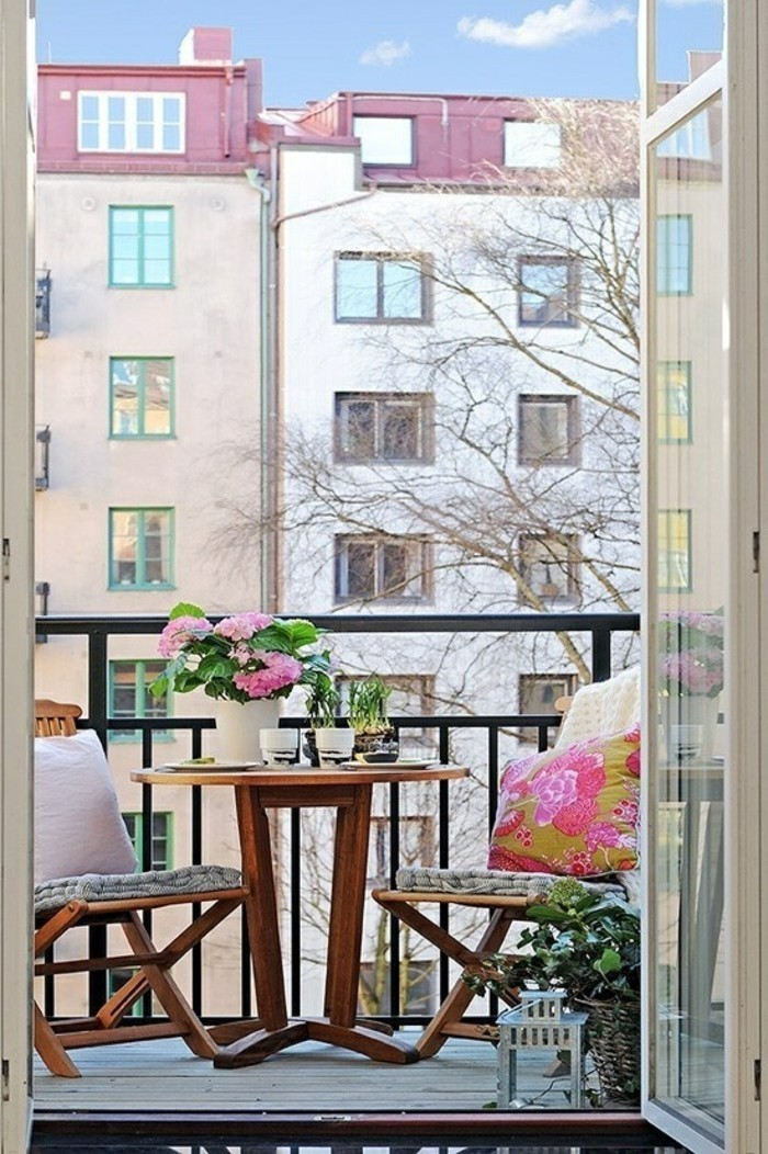 decoration balcon, bouquet de fleurs rose, tables ronde, chaises en bois, coussins décoratifs