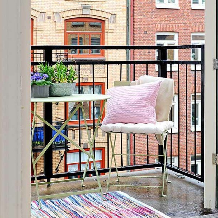 idee deco terrasse, chaise pliante, housse de coussin blanche, coussin rose, tapis multicolore