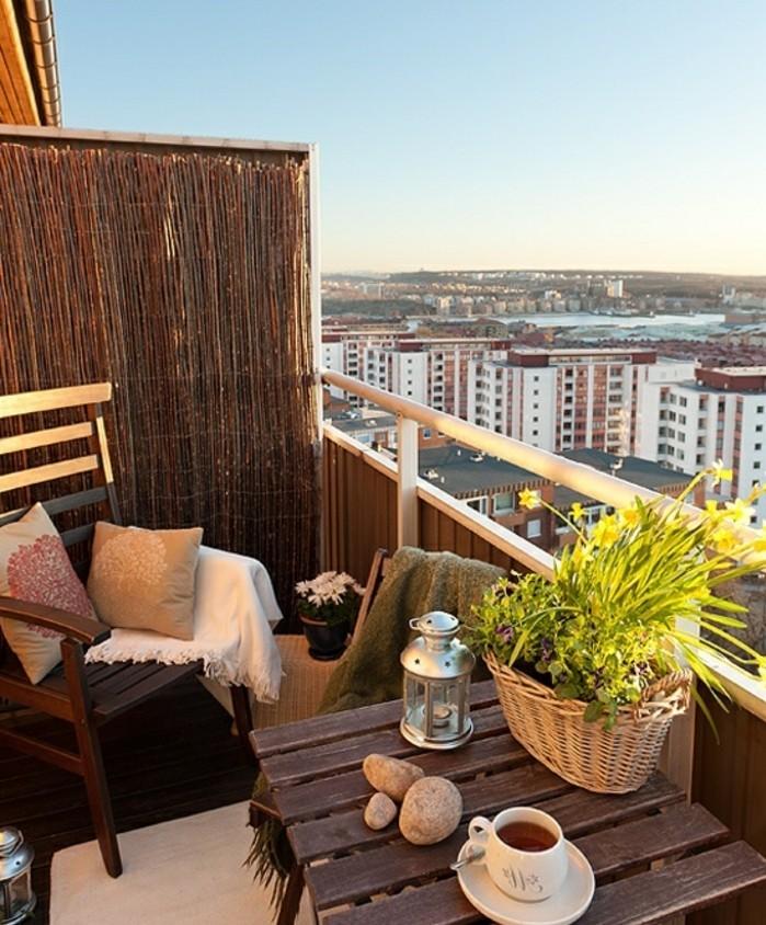 aménager un petit balcon, tasse de thé, coucher de soleil, coussins décoratifs, lanterne à bougie