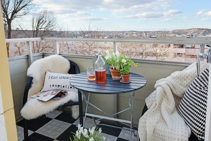 deco balcon, couverture en fausse fourrure, coussin à citation inspirante, table ronde noire