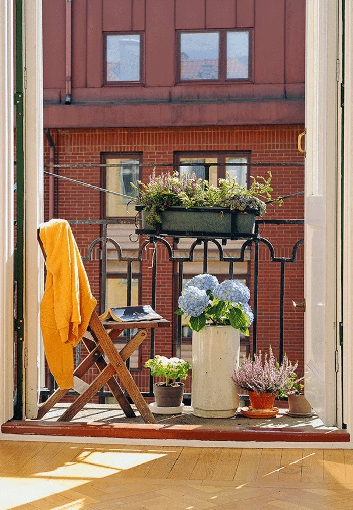decoration balcon, chaise pliante en bois, rayons du soleil, balcon fleuri