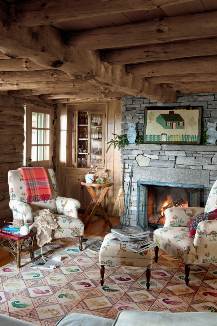ambiance cocooning, cheminée allumée, plafond avec poutres en bois, fauteuils blancs vintages, table basse