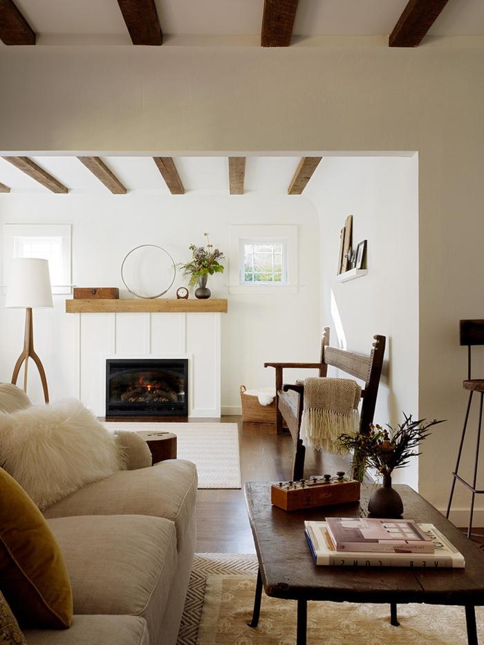déco salon cocooning, plafond avec poutres en bois, murs blancs, table basse, canapé cocooning beige