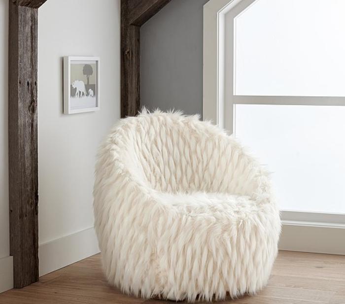 idée déco salon, parquet en bois, murs blancs, grande fenêtre, pouf blanc en fausse fourrure