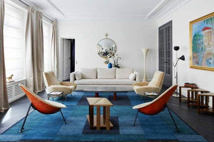 déco zen, tapis bleu, rideaux longs, murs blancs, fauteuils beige, miroir rond, portes grises