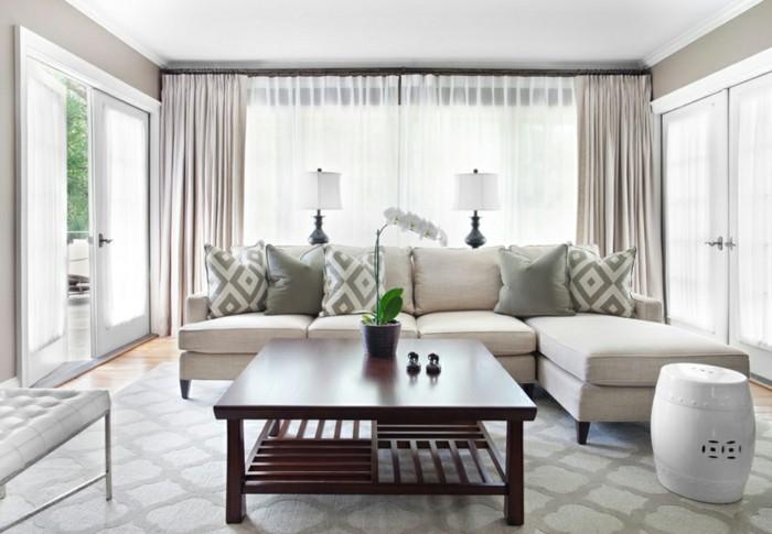 feng shui salon, table en bois foncée, rideaux longs, coussins gris et blanc, orchidée blanche