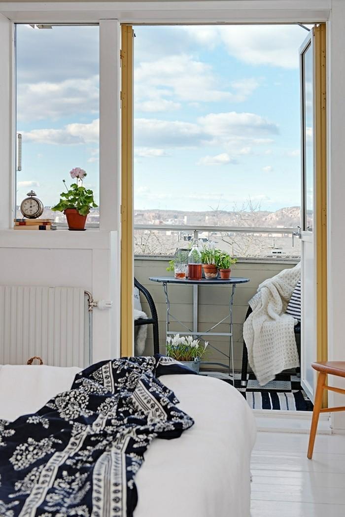 decoration balcon, table ronde, chaises noires, pot à fleur céramique, coussin blanc et noir