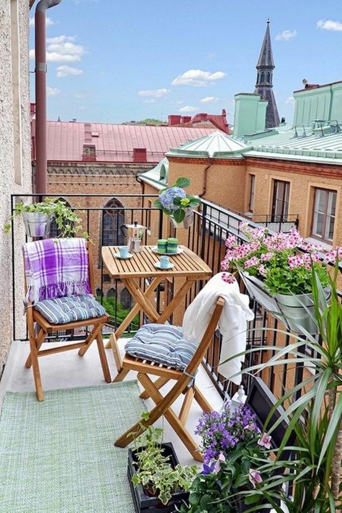 idee deco terrasse, tapis vert, table pliante, chaises en bois, housse de coussins bleues