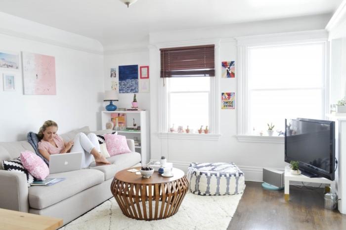 tapis cocooning, canapé gris, grandes fenêtres, pouf blanc et noir, coussins rose, table ronde