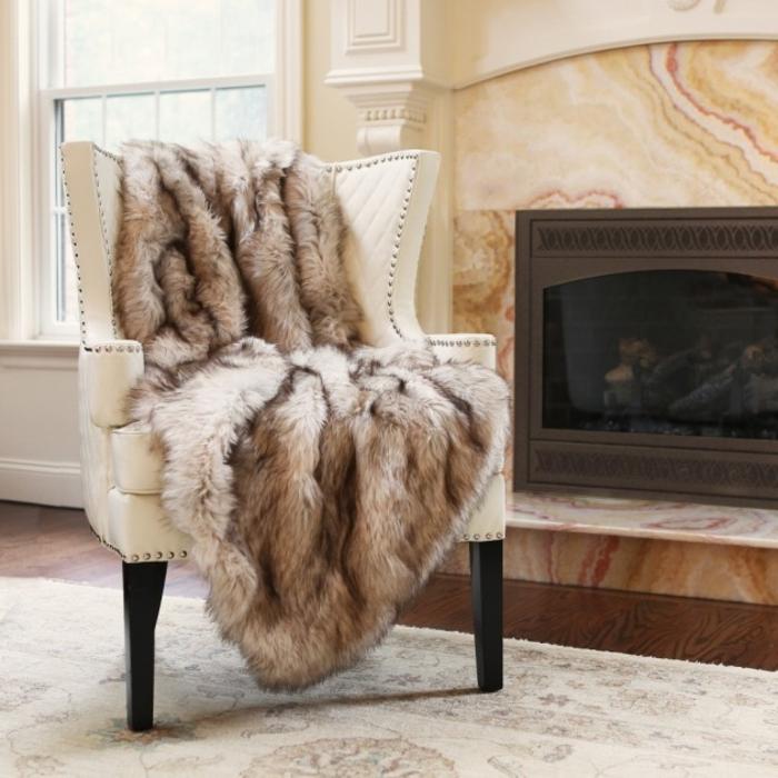 idee deco cocooning, tapis beige, parquet en bois, cheminée, fauteuil taupe, plaid en fausse fourrure