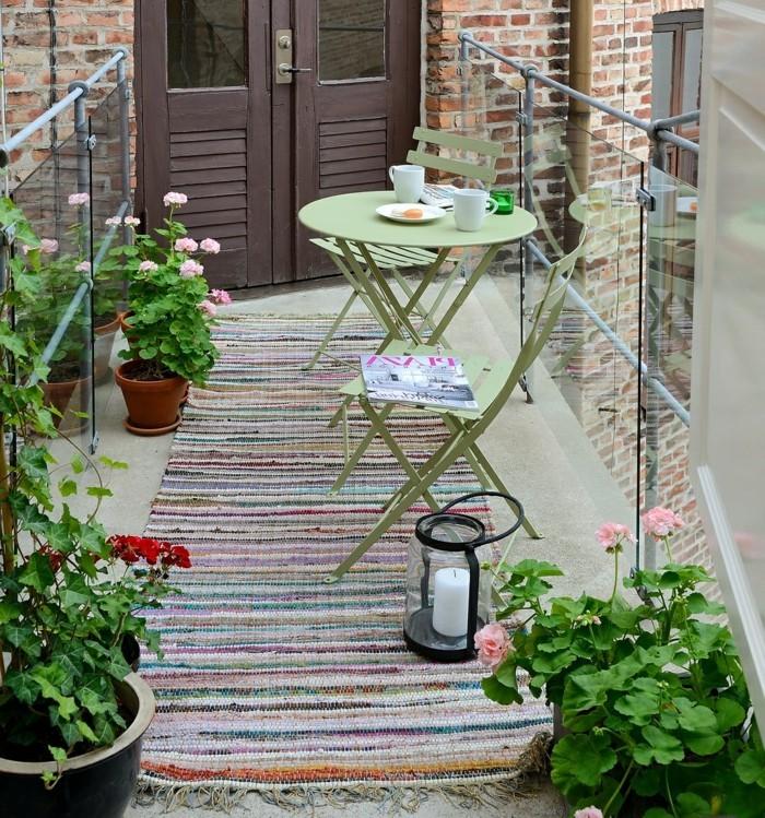 idee deco terrasse, tapis vieux multicolore, plantes vertes, porte marron, table ronde en vert