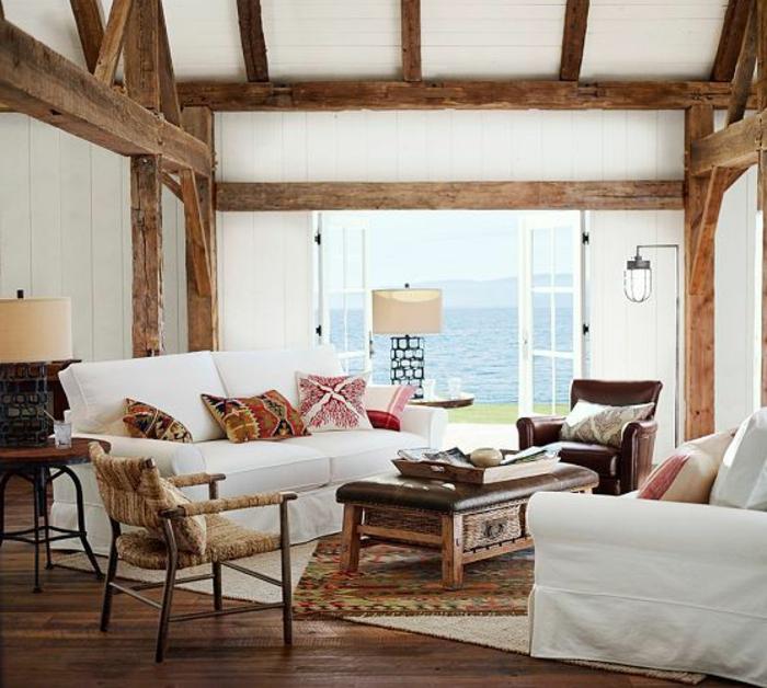 idée déco salon, plafond avec poutres en bois, murs blancs, coussins à motifs ethniques, fauteuil en cuir marron
