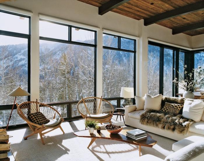 tapis cocooning, grandes fenêtres, plafond avec poutres en bois, chaises rondes, canapé blanc, coussins décoratifs