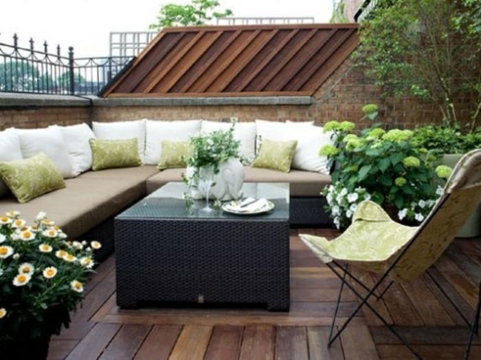 terrasse bois composite, table noire, chaise pliante, canapé d angle, coussins blancs et verts, plantes, exemple de terrasse tropezienne