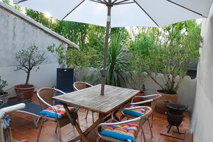 terrasse tropézienne, parasol, chaises et table en bois, plantes, carrelage, grès cérame, coussins de chaise arc en ciel, barbecue,