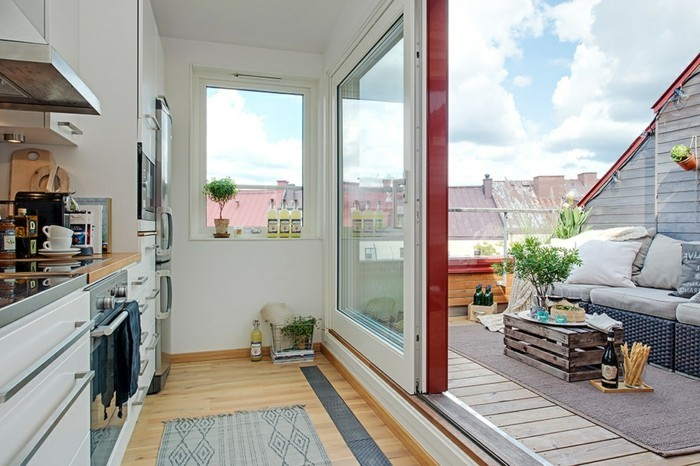 amenagement terrasse tropezienne, cuisine ouverte sur une un coin détente, canapé, table basse récup de caisson, tapis gris