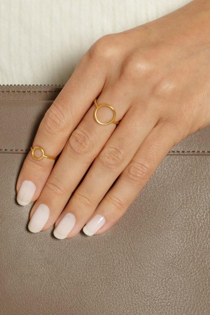 une fine bague sur le bout du doigt combiné avec un anneau identique, une manucure élégante couleur nude