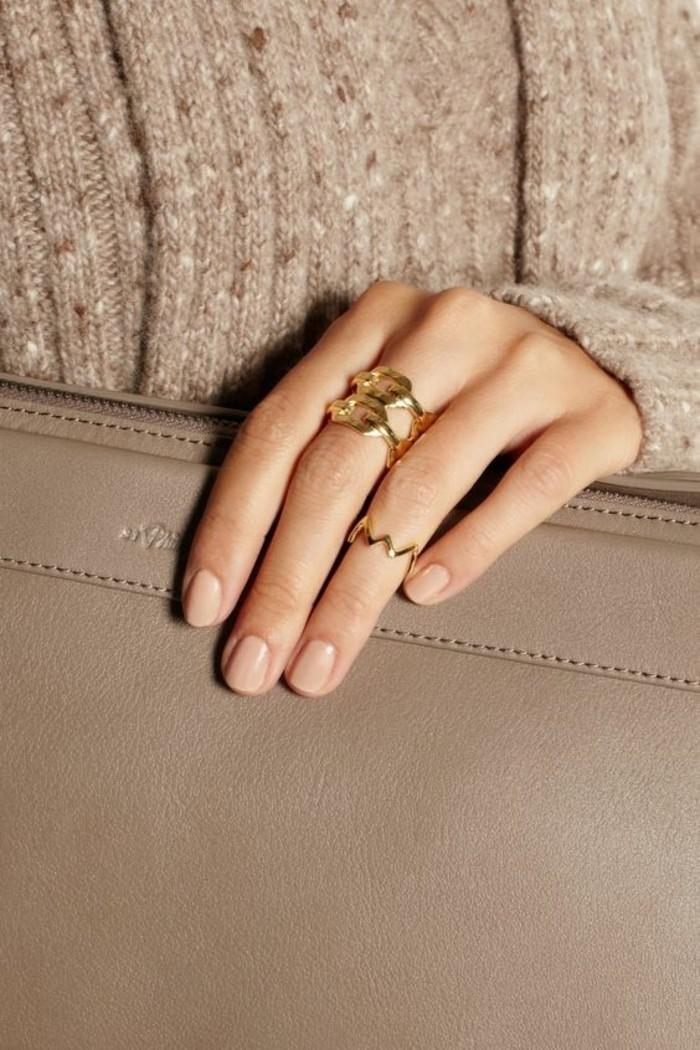 une bague phalange dorée portée de style simple et élégant, associer une bague fine à une grosse bague