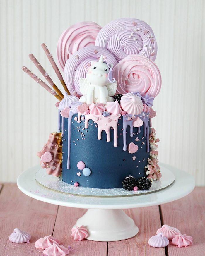 modele gateau licorne original avec creme bleue lisse, decoration gateau meringues et figurine licorne en pate à sucre