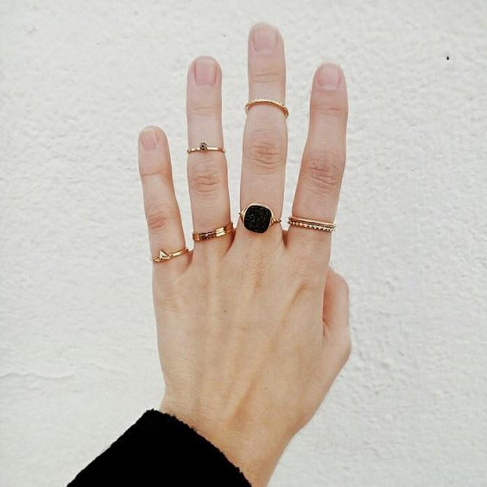 une fine bague dorée portée sur le bout du doigt, tendance bague sur chaque doigt