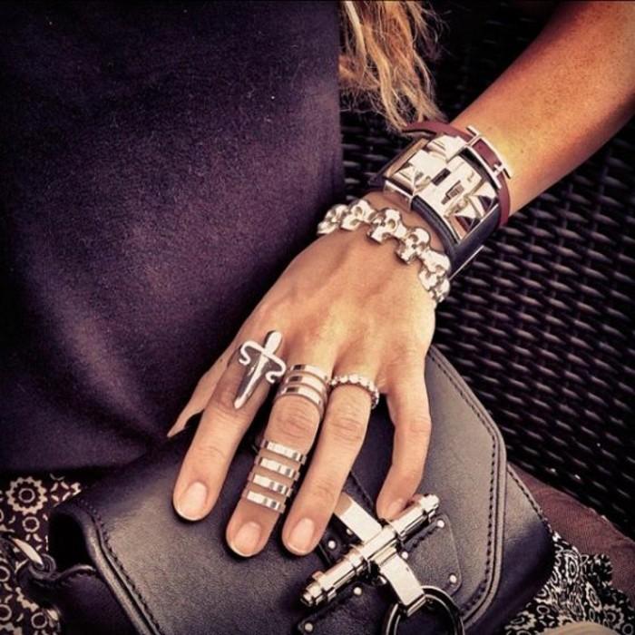 des bagues massives de style rock associées à des bracelets imposants, une grosse bague demi-doigt argentée