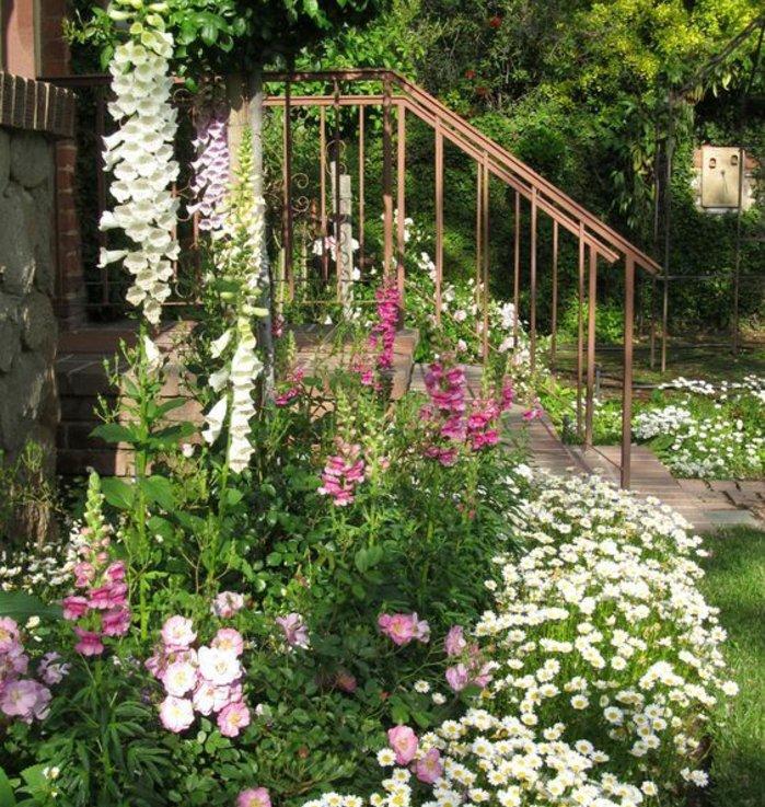 bordure parterre de fleurs conte le mur extérieur d'une maison, fleurs blanches et roses, aménagement jardin maison rustique