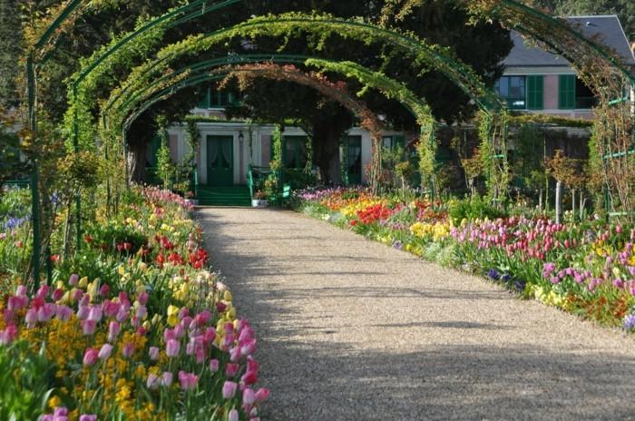 bordure parterre de fleurs, deux rangées de tulipes de couleurs diverses, une tonnelle de jardin, maison rustique de campagne