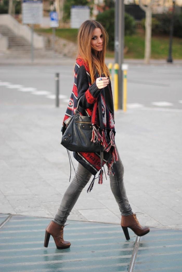 tenue jean noir, poncho rouge et noir, manucure foncée, cheveux cuivrés, sac à main en cuir
