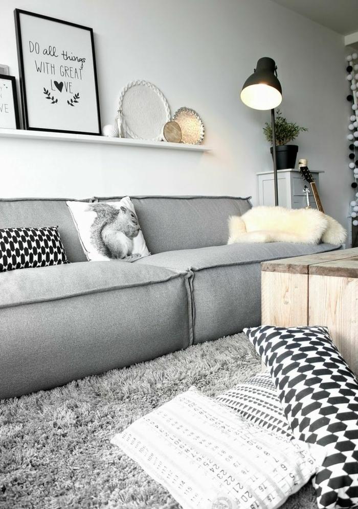 salon cocooning, lampe noire, canapé gris, coussins décoratifs, table en bois, tapis en fausse fourrure