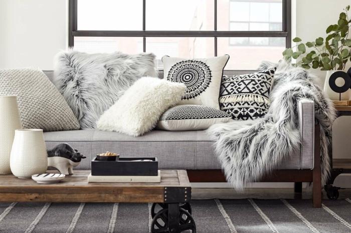 décoration intérieure salon, tapis gris, coussins décoratifs en fausse fourrure, murs blancs, grandes fenêtres
