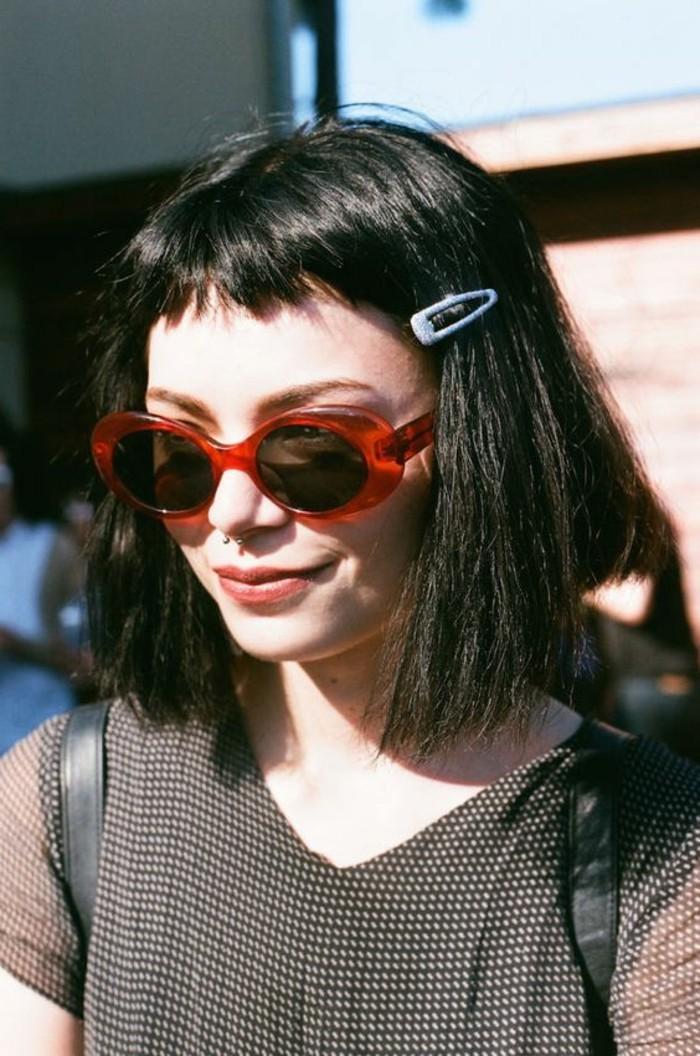 coiffure femme frange, carré cheveux couleur noir et lunettes de soleil rouges