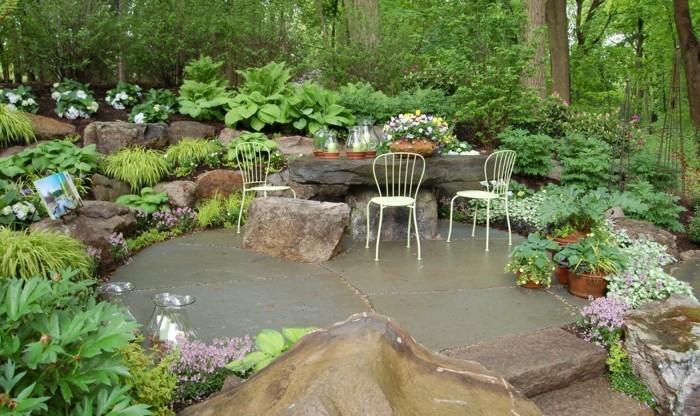 coin-detente-en-plein-air-table-en-pierre-chaises-en-métal-espace-entouré-de-rocaille-fleurie-vegetation-abondante