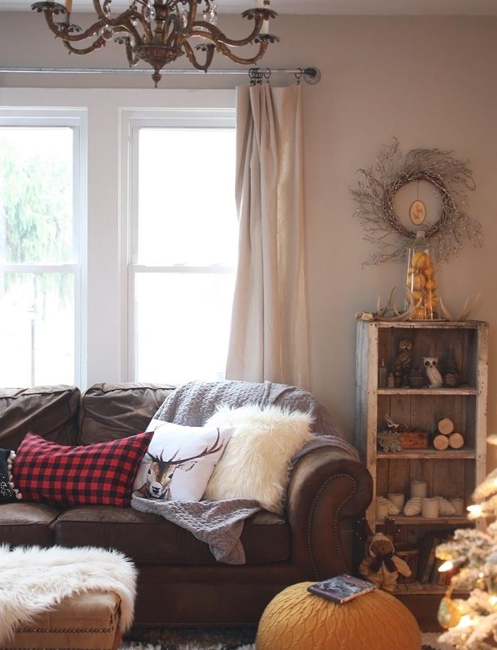 salon cocooning, meuble en palette, canapé marron, coussins décoratifs, pouf orange