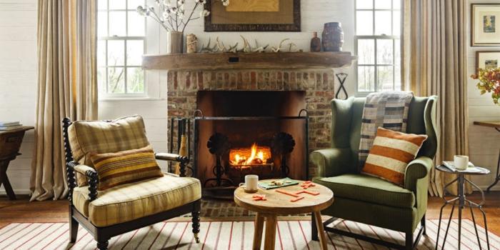 idee deco salon cocooning, cheminée en pierre, murs blancs, rideaux longs, fauteuils en bois foncé, table ronde
