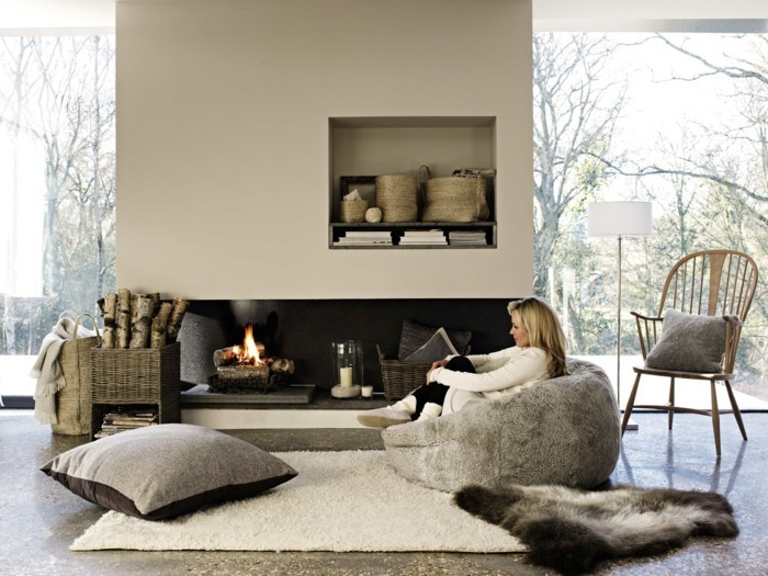 amenagement salon, grand pouf en fausse fourrure, cheminée allumée, chaise en bois, grandes fenêtres