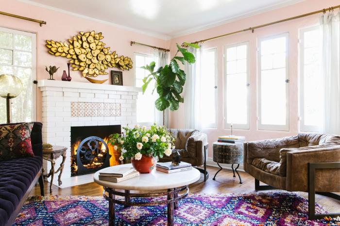 idée déco salon, table ronde, cheminée allumée, grandes fenêtres, fauteuil en cuir, plantes vertes