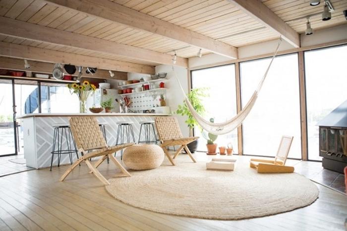 salon cocooning, tapis ronde, hamac blanc, plafond avec poutres en bois, plantes vertes, cheminée