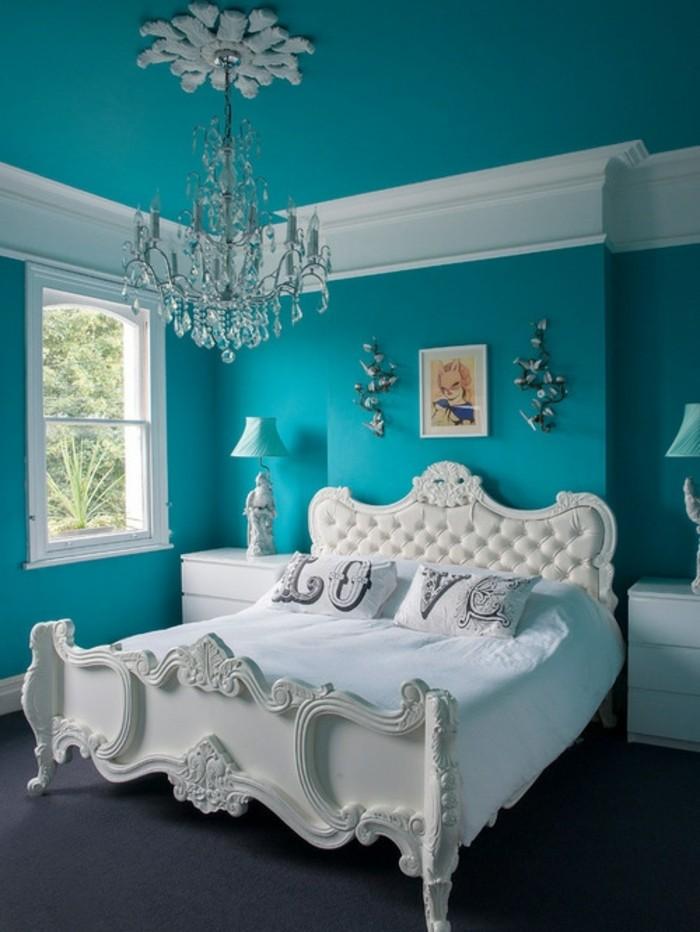 chambre turquoise, lustre en cristaux, tête de lit en cuir et bois, tapis foncé