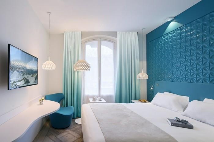 chambre turquoise, grande fenêtre, fauteuil turquoise, couverture de lit blanche
