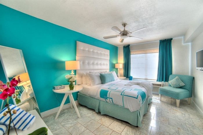 chambre turquoise, ventilateur de plafond, orchidée rouge, coussins décoratifs