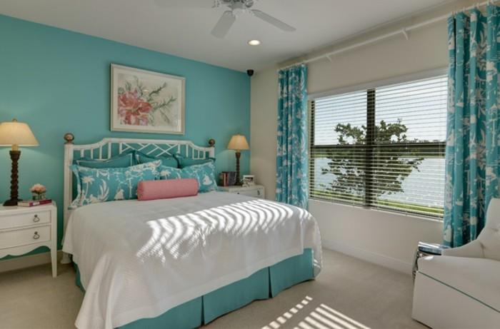 chambre turquoise, grande fenêtre, lampes de chevet, fauteuil et lit blancs
