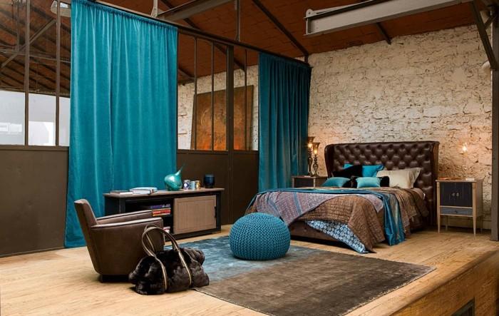 deco chambre adulte bleu et marron, fauteuil en cuir, pouf turquoise, rideaux longs