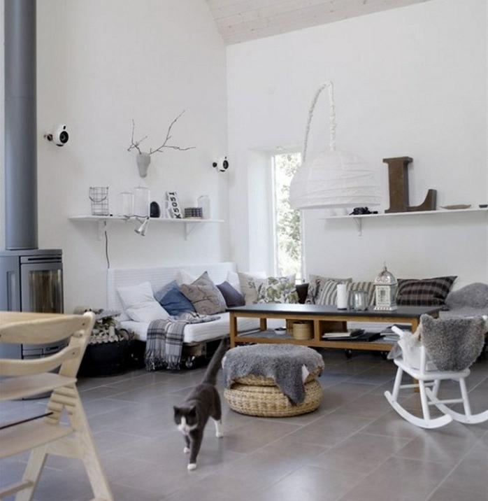 déco cocooning salon, chaise à bascule, canapé blanc, coussins décoratifs, cheminée grise, murs blancs