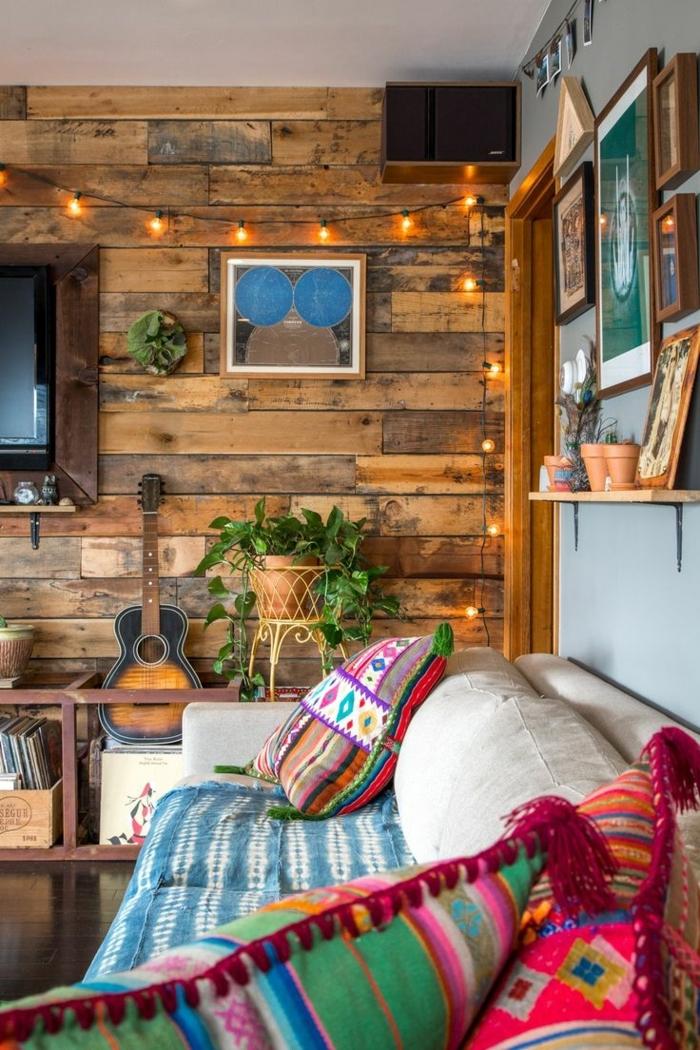amenagement salon, canapé beige, murs en bois, plantes vertes, guirlande lumineuse, cadres photos en bois
