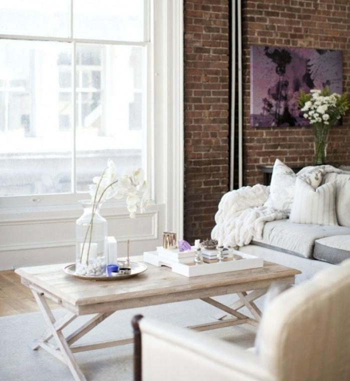 ambiance cocooning, tapis blanc, murs en briques, grande fenêtre, plaid en crochet, canapé gris