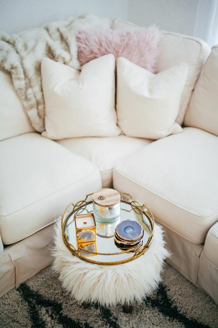 idée déco salon, pouf en fausse fourrure, canapé d'angle, coussins décoratifs beiges, bougies