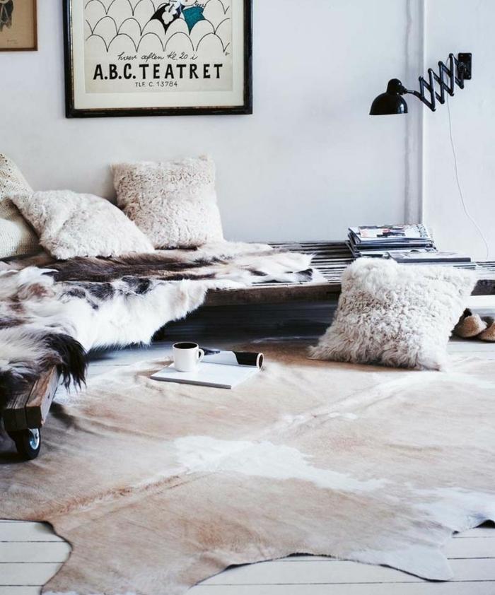 salon cocooning, coussins en fausse fourrure, peinture avec cadre noir, tasse de café, magazine