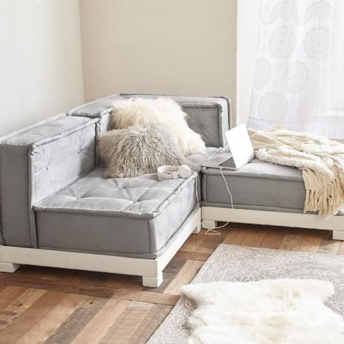 décoration intérieure salon, canapé d'angle gris, tapis en fausse fourrure, rideaux blancs